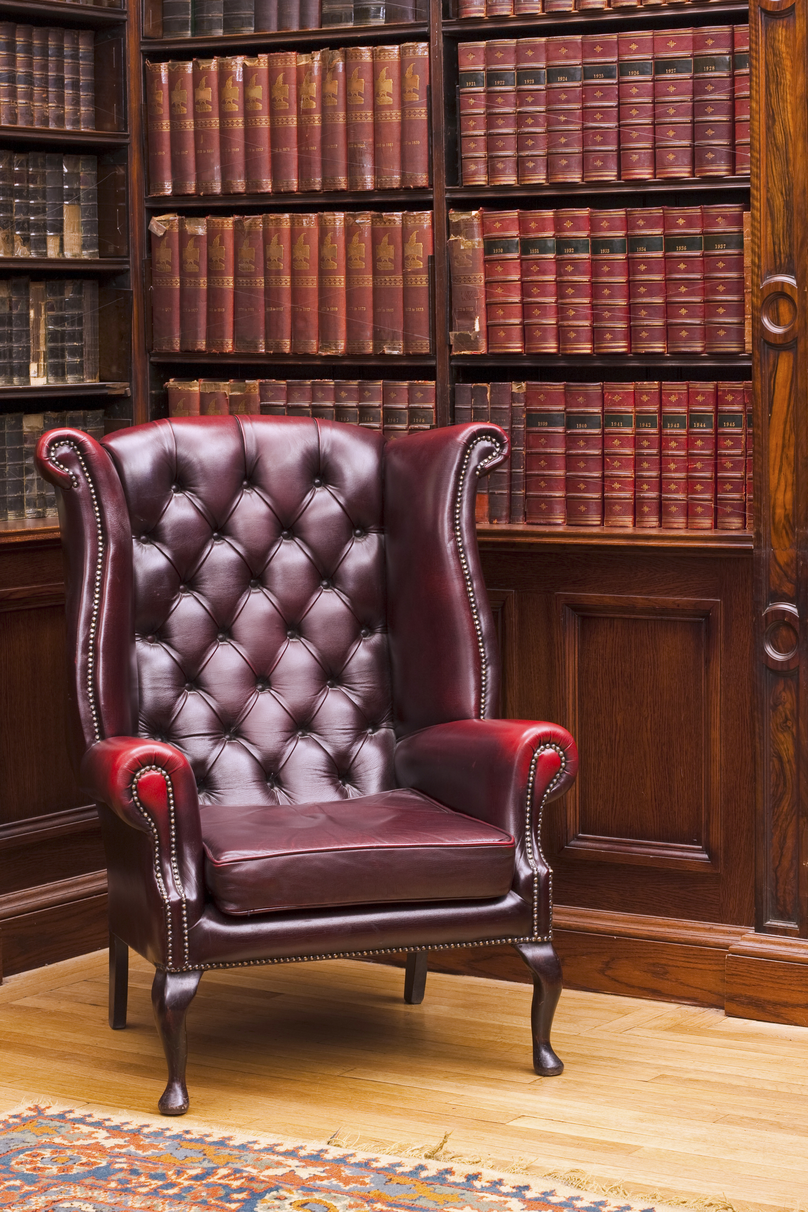 Traditional Chesterfield chair in classical library room