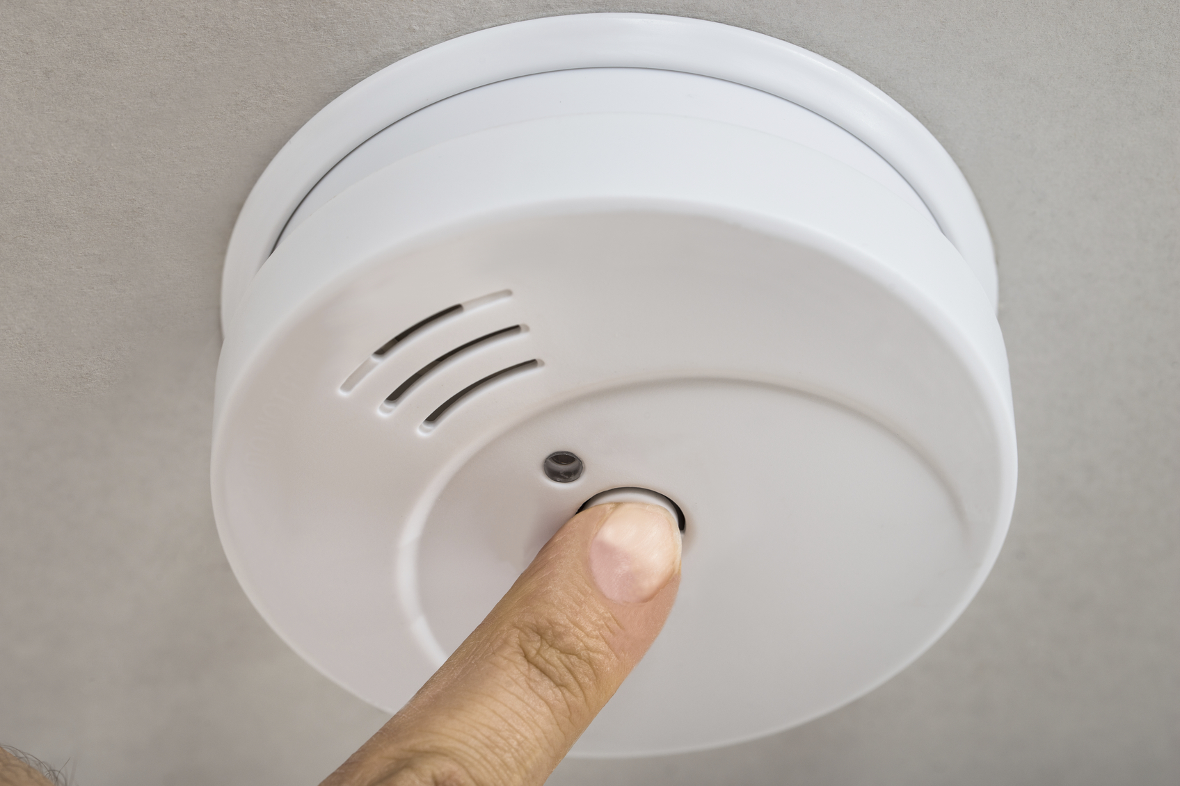 Close-up Photo Of Finger Testing Smoke Detector