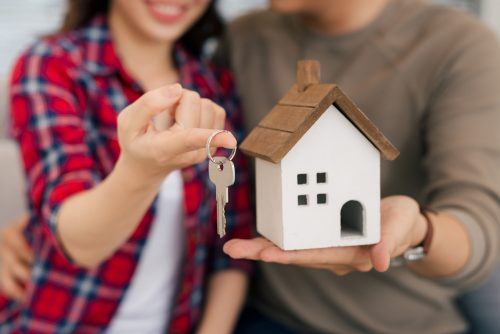 Proud young couple with keys and wooden house modelling