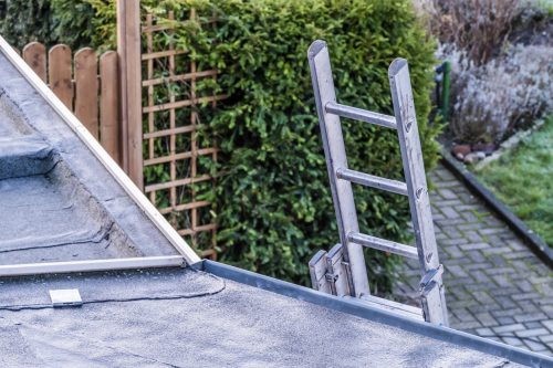 Top view of a long silver aluminum ladder leaning against the wall of the house