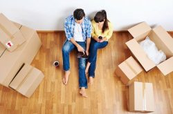 a young couple sitting down in their new home amongst boxes of belongings
