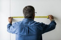 a man measuring a wall