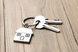 keys attached to a house-shaped keyring on a wooden background