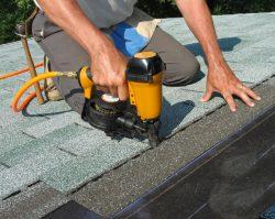 Man using nail gun to apply asphalt shingles to a roof