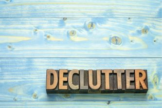 a wooden block that states 'declutter', in front of a light blue wooden background
