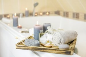 A bath with candles, bath essentials and a towel