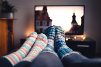 A couple cosying up on the sofa wearing slipper socks and watching TV