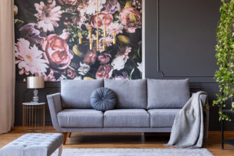 Cushion and blanket on a stylish sofa in a grey living room interior with ivy plant and flowers print on the wall. Maximalist style